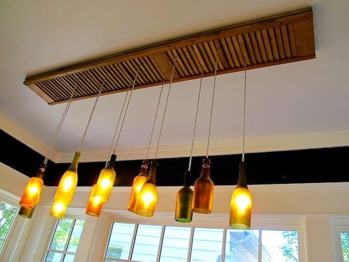 Bifold bathroom door and discarded wine and beer bottles become a charming chandelier